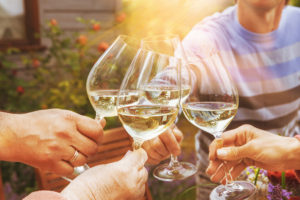 close up of hands toast with glasses of white wine