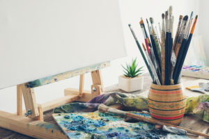 Artistic equipment in studio: canvas on wooden easel, paint brushes, paints and used palette.