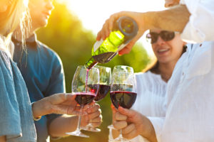 people in sunny vineyard pouring red wine into glass during fall harvest