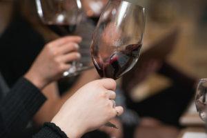 Oregon Wine Passport at wine tasting, people hold glasses of red wine