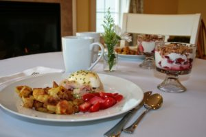 a table with a breakfast of eggs benedict and fruit parfait