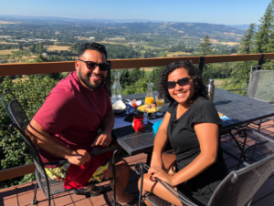 a man and a woman sitting at a table on a deck overlooking a valley